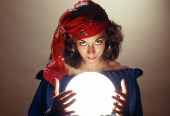 Fortune teller smiling over her crystal ball.